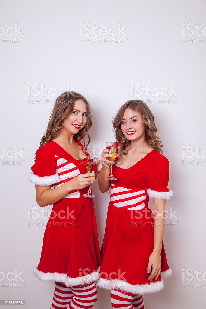 Beautiful Happy two women in Santa Claus clothes with champagne foto de stock royalty-free