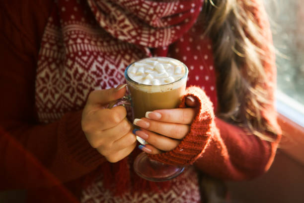 beautiful happy woman drinking cup of coffee sitting home by the window. christmas morning. christmas drink - hot chocolate stock photos and pictures