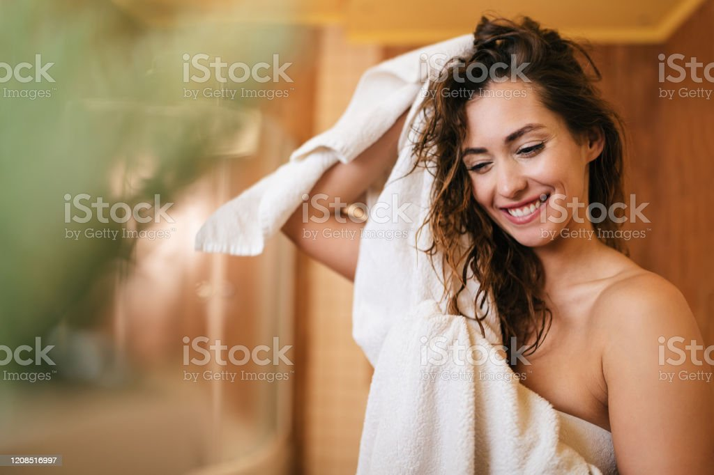 Beautiful happy woman drying her hair with a towel in the bathroom. Young beautiful woman using towel and drying her hair in the bathroom. Adult Stock Photo