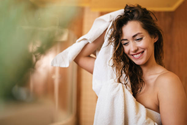 Beautiful happy woman drying her hair with a towel in the bathroom. stock photo