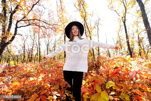 beautiful happy woman having fun in park on autumn sunny day. wide angle