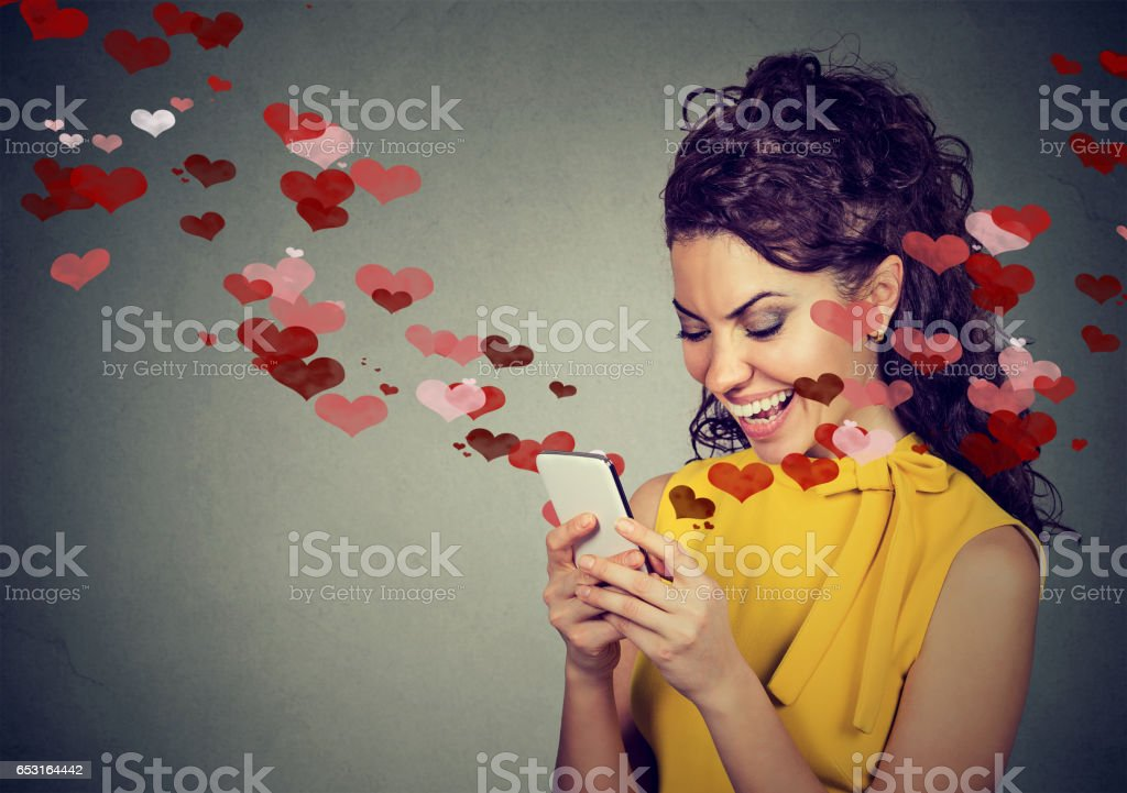 Beautiful happy woman sending love text message on mobile phone with red hearts stock photo