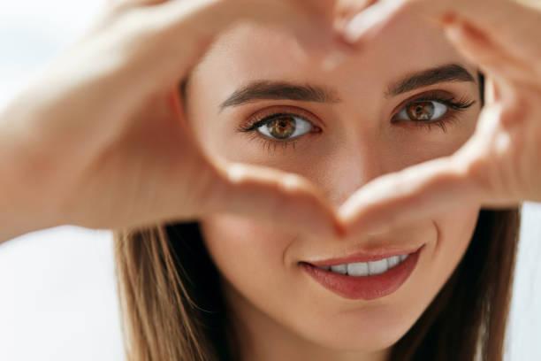 linda mulher feliz mostrando sinal de amor perto de olhos. - visao - fotografias e filmes do acervo