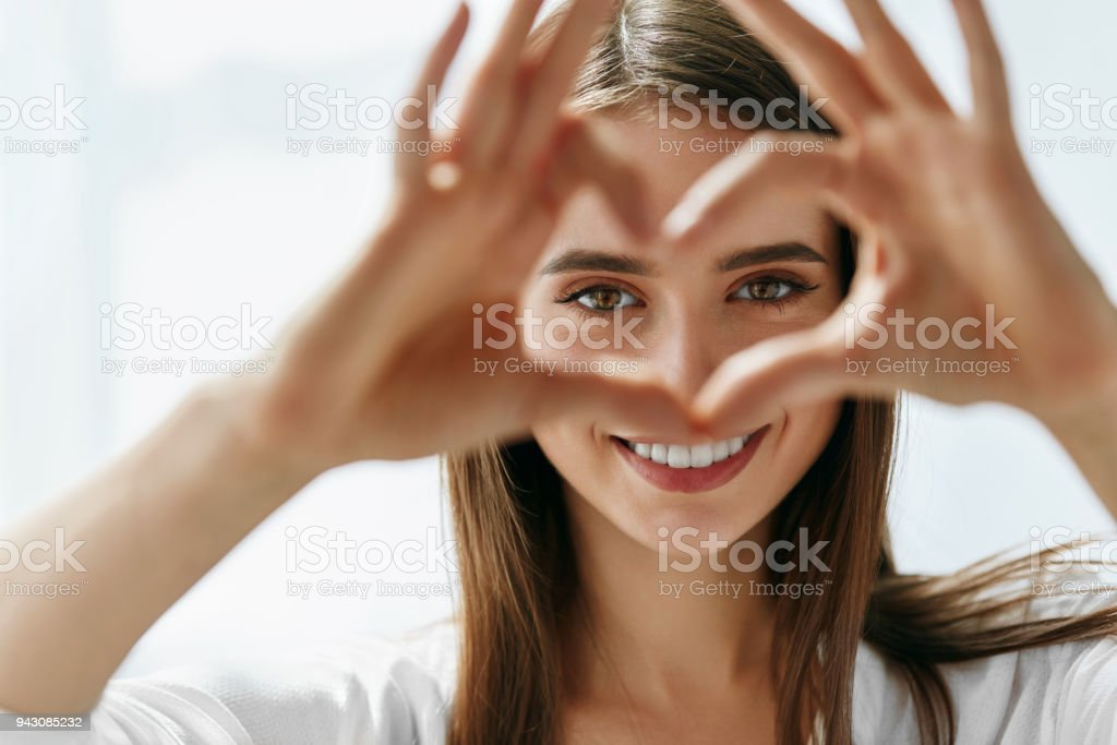 Beautiful Happy Woman Showing Love Sign Near Eyes. foto stock royalty-free