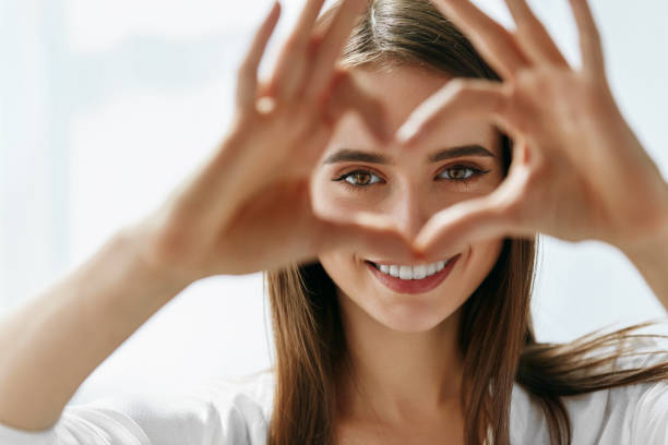 beautiful happy woman showing love sign near eyes. - eye stock pictures, royalty-free photos & images