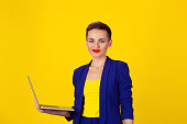 Beautiful happy woman  smiling kindly standing with laptop over yellow background