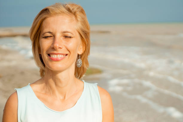 Beautiful happy woman smiling with closed eyes on the sea shore, closeup portrait. stock photo