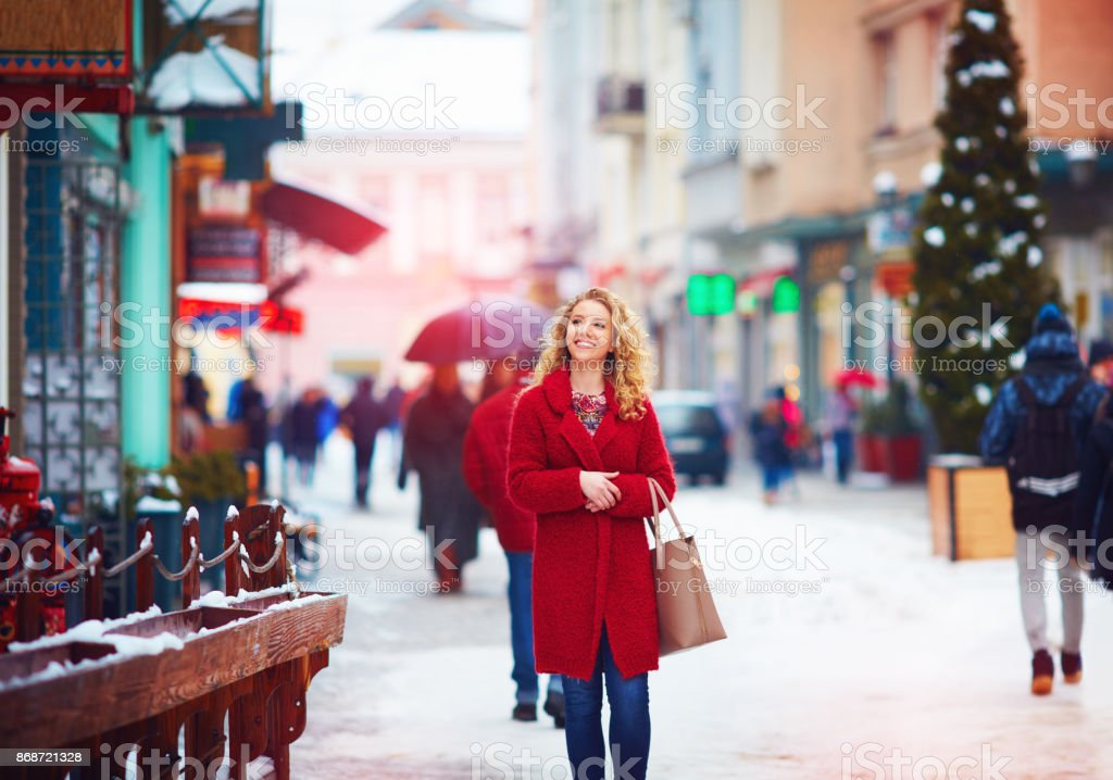 beautiful happy woman walking on crowded city street in winter