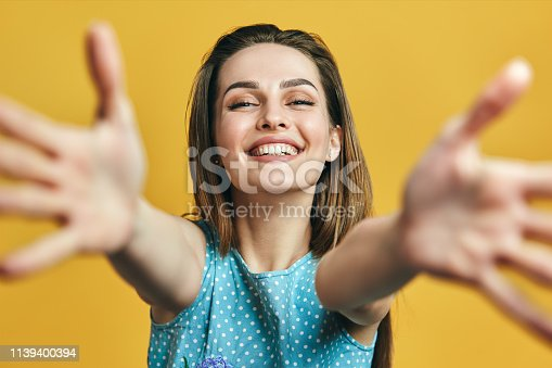 Beautiful happy woman with open hand ready for hugs on yellow background