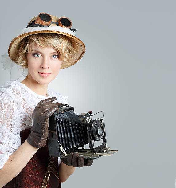 beautiful happy woman with retro camera. - steampunk fashion stock photos and pictures