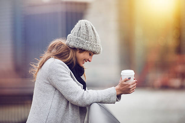 beautiful happy young adult woman drinking coffee outoors - gute winterjacken stock-fotos und bilder