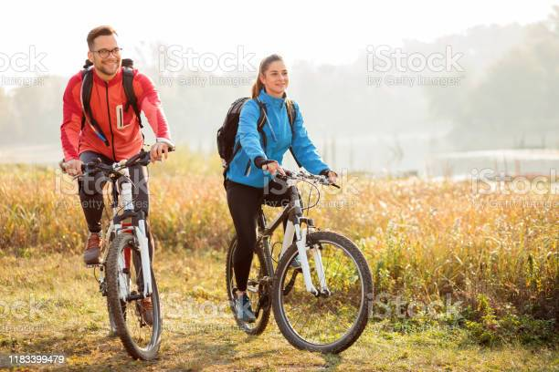 Photo of Beautiful happy young couple enjoying early morning bicycle ride by the river or lake