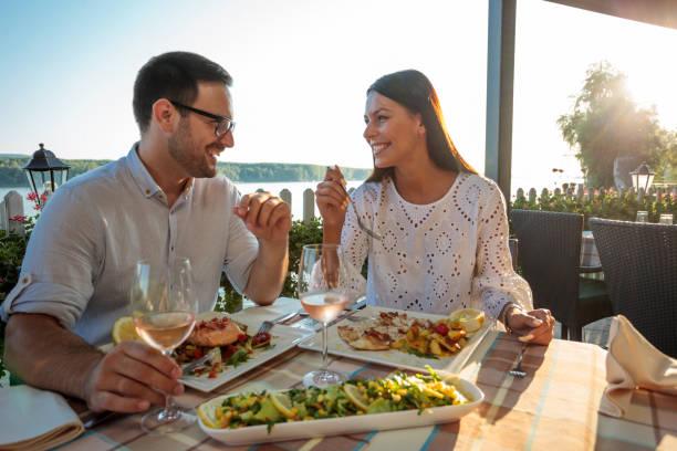 hermosa pareja joven feliz haciendo un brindis, celebrando el aniversario o el cumpleaños en un restaurante - couple lunch outdoors fotografías e imágenes de stock