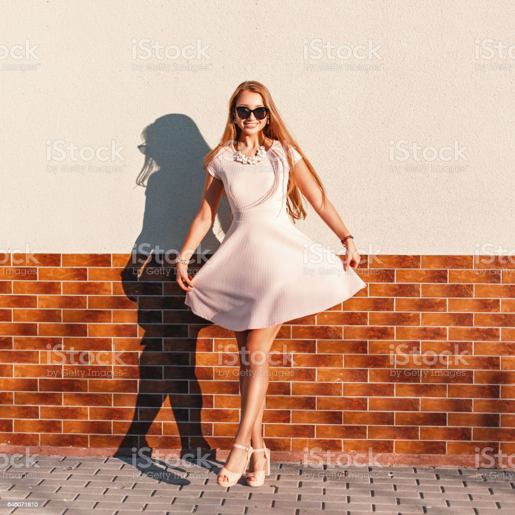 Beautiful happy young girl with a smile in a pink dress near the brick wall stock photo