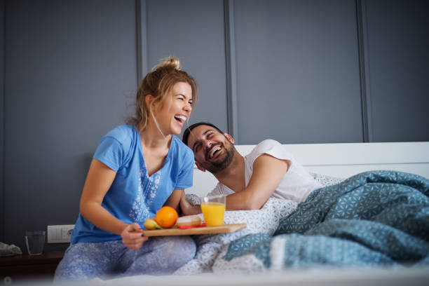 Beautiful happy young romantic girl brings breakfast to her husband in the bed and laughing together after he wakes up. stock photo
