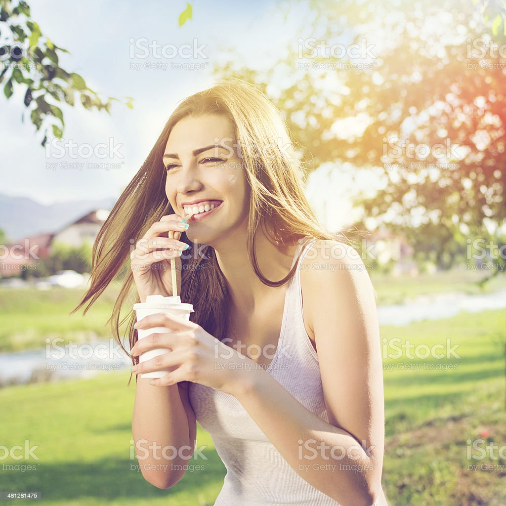 Beautiful happy young woman drinking coffee in park stock photo