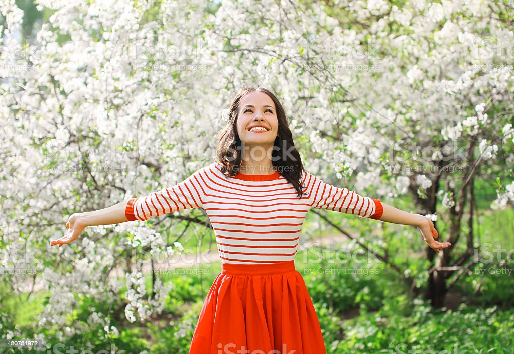 Beautiful happy young woman enjoying smell in a flowering spring stock photo