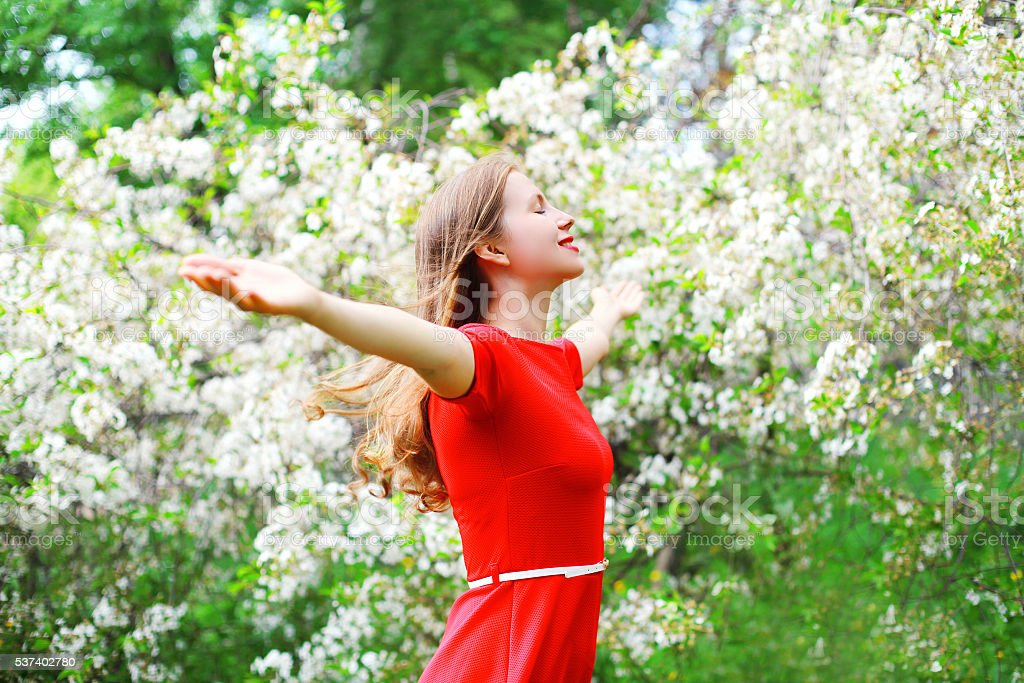 Beautiful happy young woman enjoying smell in flowering garden stock photo