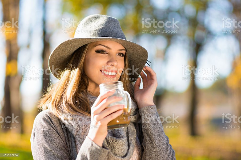 Beautiful happy young woman in park holding glass coffee mug stock photo