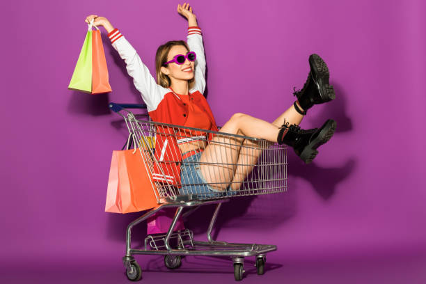 beautiful happy young woman in sunglasses holding paper bags and sitting in shopping trolley on violet stock photo