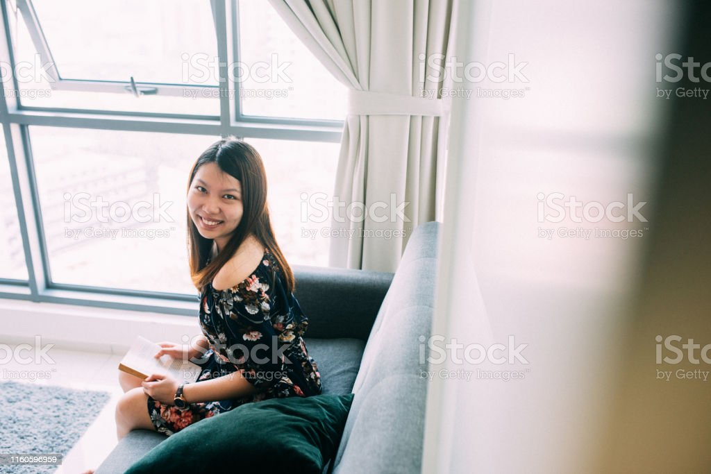 Image of Beautiful happy young woman reading a book at living room.
