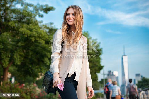 654490824 istock photo Beautiful happy young woman walking in the city park 537641266