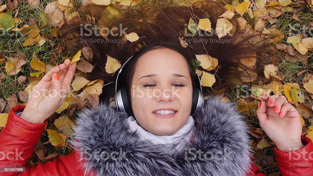 Beautiful happy young woman with headphones lying on autumn leaves foto stock royalty-free