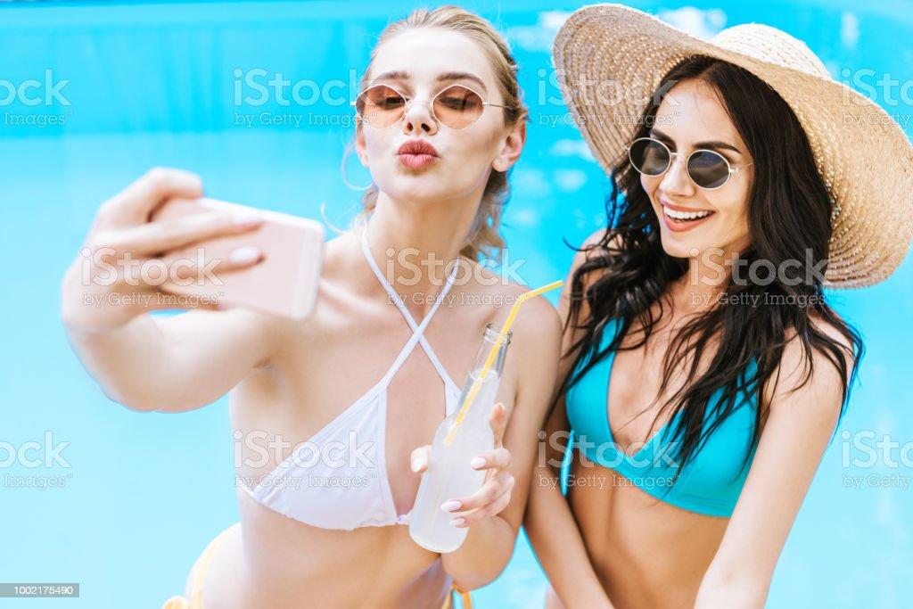 e1b61a9a5 hermosas felizes mujeres jóvenes en traje de baño tomando selfie con  smartphone cerca de piscina foto
