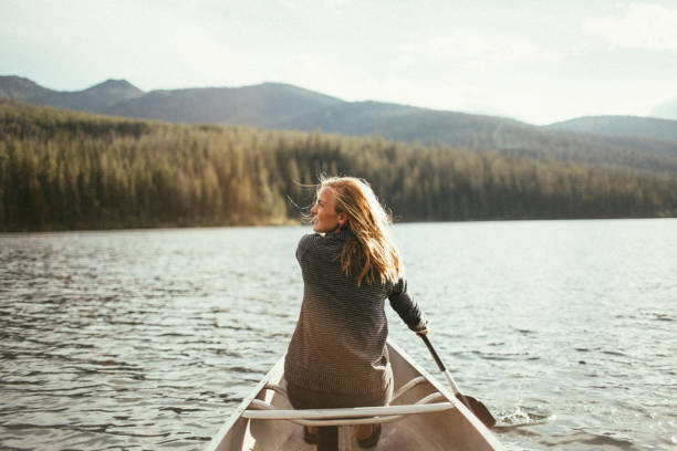 Beautiful healthy active woman canoeing on a lake at sunset stock photo