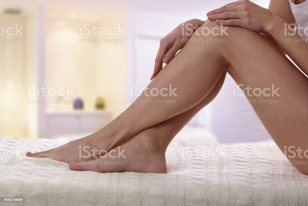 Beautiful, healthy and sensual woman enjoying in a smooth touch of her skin. Female legs Waxing, Hair Removal, Skin care concept stock photo