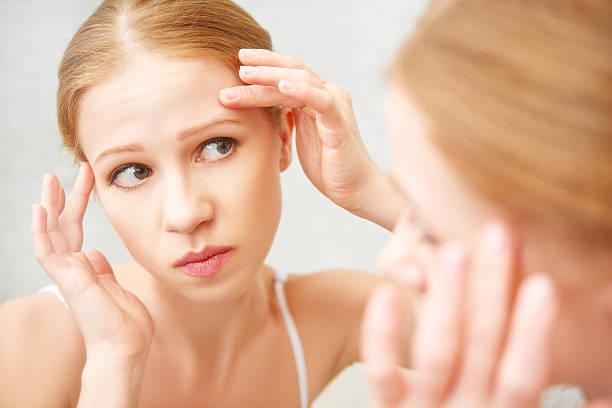 Linda mulher saudável assustada viu no espelho para acne - foto de acervo