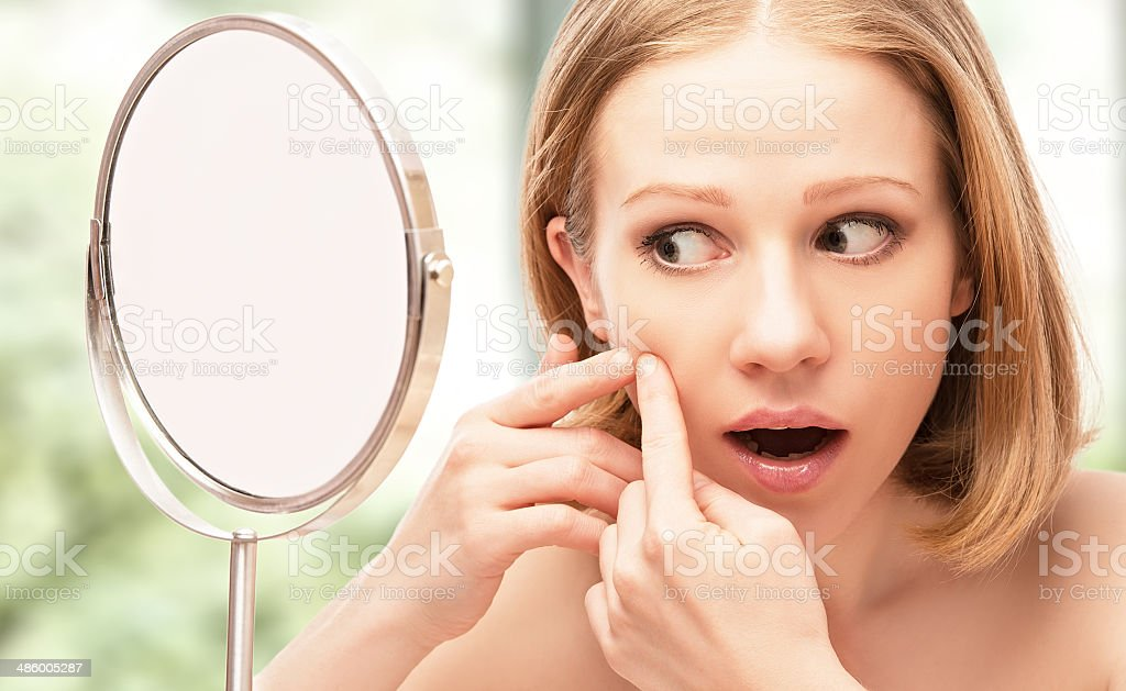 beautiful healthy woman  frightened saw in the mirror acne royalty-free stock photo