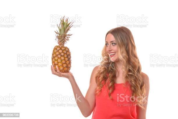 Piękna Zdrowa Młoda Kobieta Patrząca Na Ananasa - zdjęcia stockowe i więcej obrazów Ananas