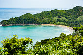 View of a small crescent beach hidden away among green hills and forests.  Punta Islita Beach, Guanacaste, Costa Rica