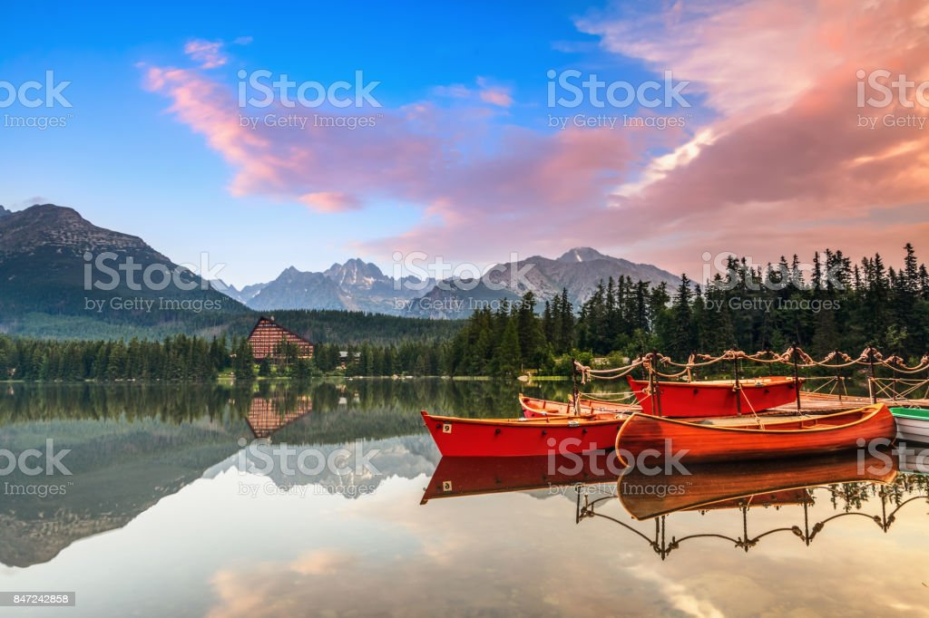 Beautiful high mountains around the incredibly magic lake with red boats and canoe on a spring day. stock photo