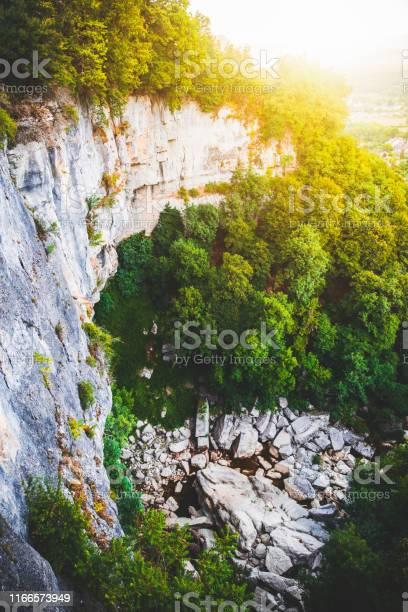 Photo of Beautiful high point of view on Cerveyrieu waterfall in french Bugey region in Ain, dry in summer and during a bright sunset in forest