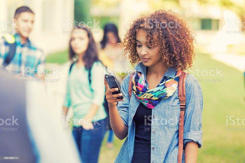 Beautiful high school student using smart phone outdoors stock photo