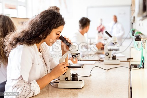 istock Beautiful high school student with microscope in laboratory. 841550782