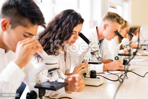 1097006206 istock photo Beautiful high school students with microscopes in laboratory. 846410832