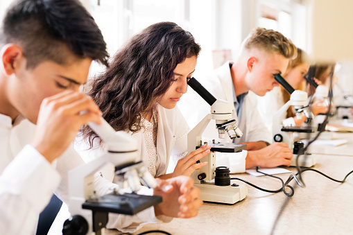 457224763 istock photo Beautiful high school students with microscopes in laboratory. 846410832