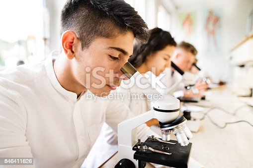 1097006206 istock photo Beautiful high school students with microscopes in laboratory. 846411626