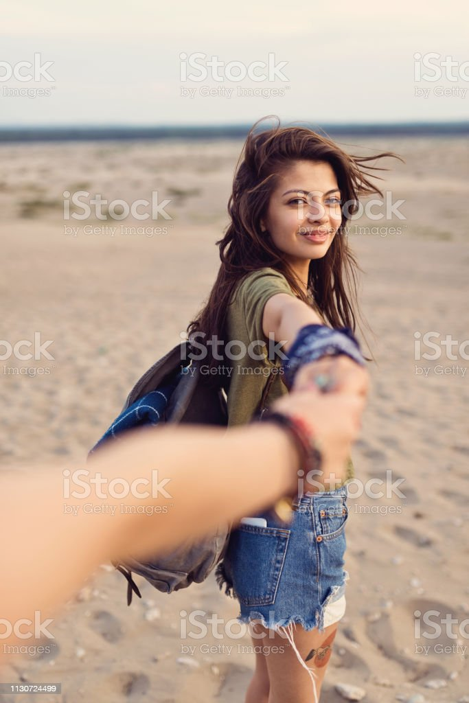 Beautiful hiker holding friend's hand in desert Portrait of beautiful young woman holding friend's hand. Female is smiling while enjoying adventure in desert. She is having brown hair. 20-24 Years Stock Photo