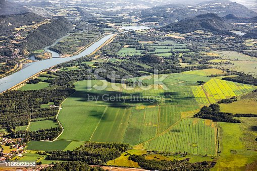 Vibrant color photography of beautiful hilly French landscape aerial view in middle of Bugey mountains in Ain near Savoie, with Rhone River, vibrant green fields and famous Lake Bourget not far. Shot from Grand Colombier mountain top during a sunny summer day, in Bugey mountains, in Ain department not far from Jura and Savoie border near Culoz city, Auvergne-Rhone-Alpes region in France (Europe).