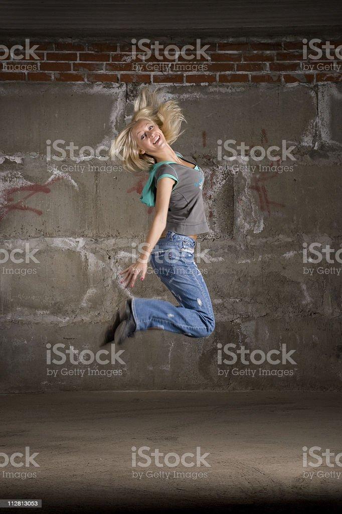 Beautiful hip hop girl dancing over brick wall stock photo