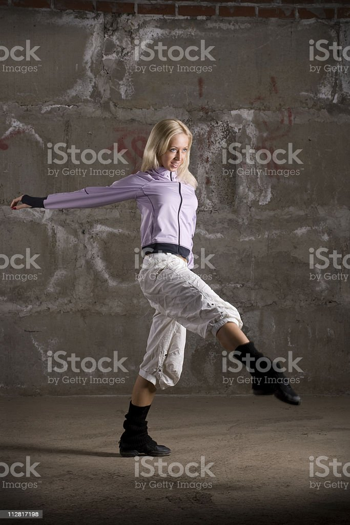 Beautiful hip hop girl dancing over grey brick wall stock photo