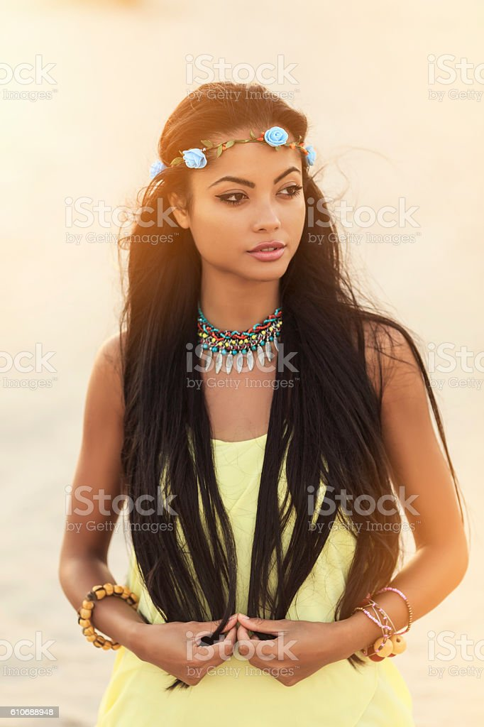 Beautiful hippie asian woman with wreath standing on beach stock photo