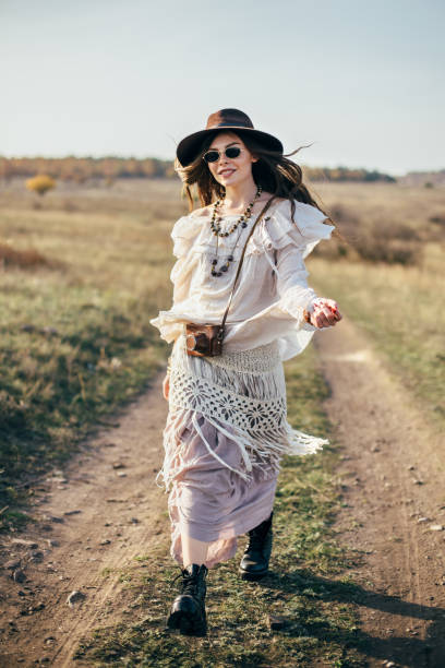 Beautiful hippie girl in hat walking on road in nature Beautiful hippie girl in hat walking on road in nature. Freedom lifestyle romani people stock pictures, royalty-free photos & images