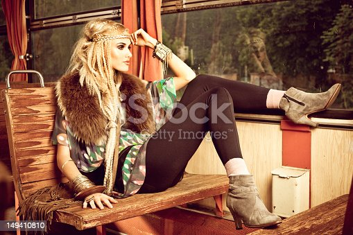 A beautiful young adult woman wearing in hippie style sitting in a vintage train and looking out the window.