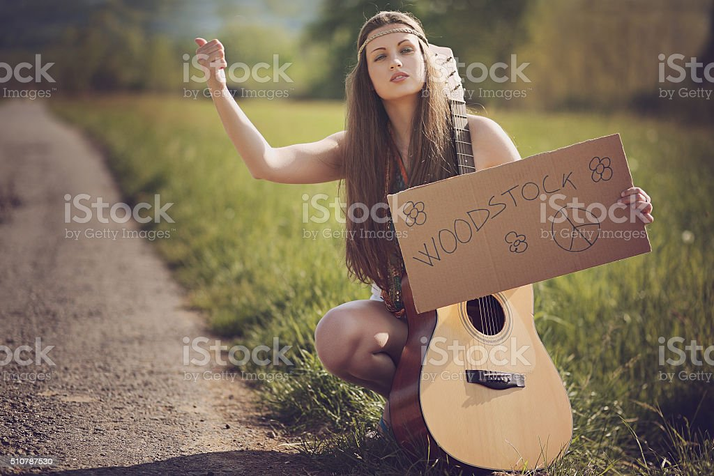 Beautiful hippie with guitar hitch-hiking stock photo