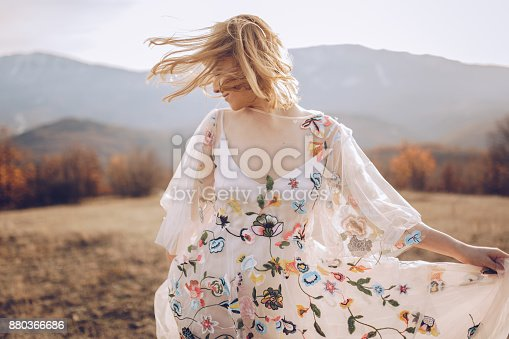 Beautiful hippie woman dancing in a meadow